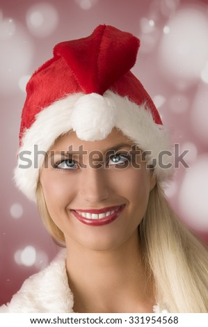 close-up funny portrait of pretty girl with christmas red Santa Claus hat posing with bizarre expression, twisted eyes.  - stock photo