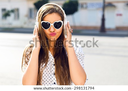 Close up funny portrait of sexy young pretty girl listening music on big earphones, wearing cute sunglasses, posing at city center at sunny summer day. - stock photo