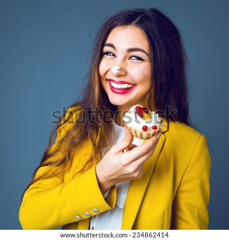 Close up funny studio portrait of young cheerful  pretty brunette woman eating tasty cake, soiled cream, smiling and having fun. Positive emotions, bright colors. - stock photo