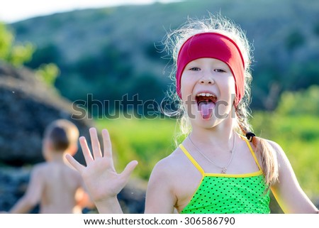 Close up Funny White Young Girl Showing her Tongue Out to Camera with Slightly Raised Hands