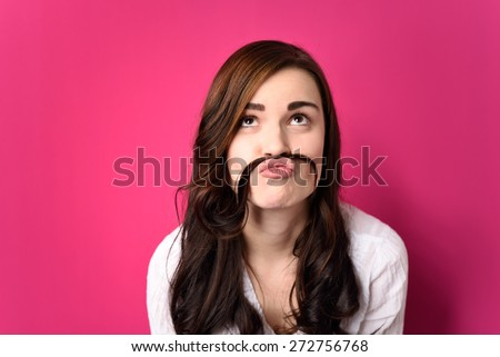 Close up Funny Young Woman Putting her Hair Between Nose and Lip and Looking Up. Isolated on a Pink Background. - stock photo