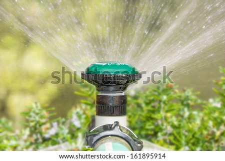 Close up,garden sprinkler head,water spray.Plastic sprayer head mounted on pipe, connected to hose.Can be rotated to 360 degrees for full spray.White arrow,numbers painted on head.Low angle view.  - stock photo