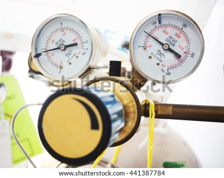 Close up gauges and valve on nitrogen gas cylinder in laboratory - stock photo