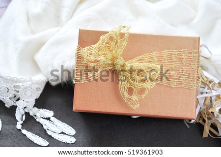 Close up gift box with golden ribbon with scarf on background