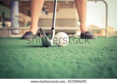 close up girl tee-off at golf driving range - stock photo