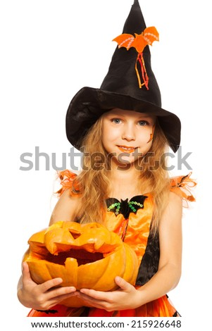 Close-up girl with pumpkin in witch dress