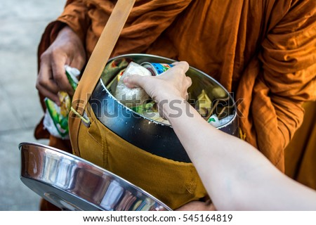 Close up : Give rice food in alms to a Buddhist monk . Hand put food to monk's alms bowl , Thailand.
