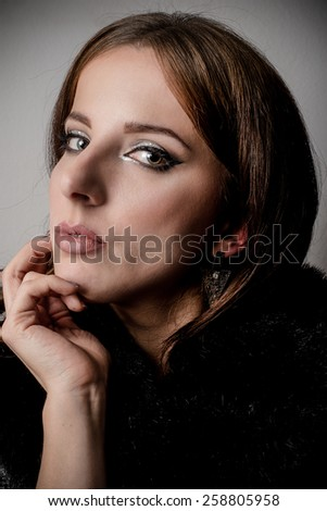 Close up Glamorous Young Woman in Black Fashion Leaning on her Hand While Looking at the Camera. Captured in Studio on a Gray Background. - stock photo