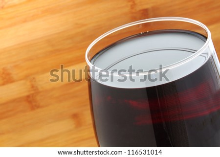 Close Up Glass of Red Wine with a wooden background