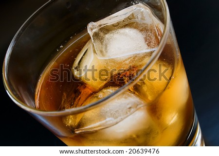 Close up glass with alcohol and ice in dark