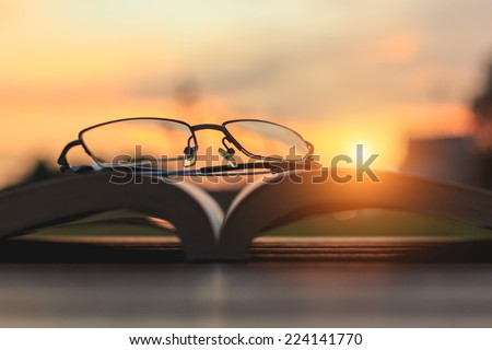 Close up glasses and book on table in sunset time - stock photo