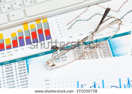 close-up glasses, on the business papers with financial charts