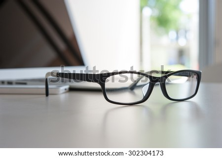 close up glasses on work desk with laptop