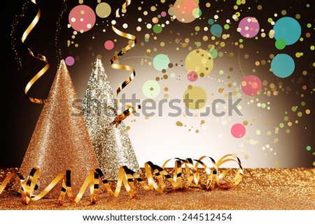 Close up Glittery Carnival Cone Hats and Gold Streamers with Confetti Effect on Glittery Table in Front Gradient Brown Background - stock photo