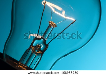 Close up glowing light bulb on blue background - stock photo
