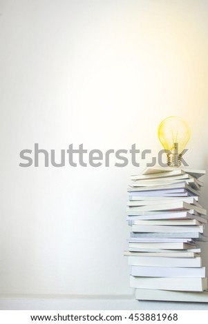 Close up glowing light bulb on book stacked  with concrete wall background , education and learning concept - stock photo