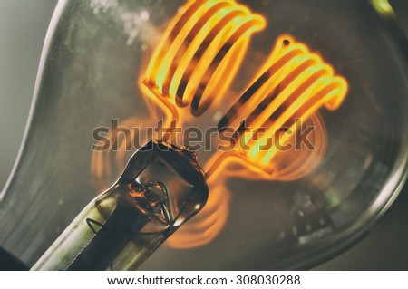 Close up glowing vintage light bulb - stock photo