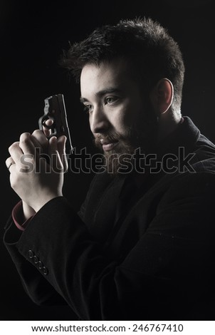 Close up Goatee Young Man Wearing Black Suit Holding Small Gun While Looking Left Side. Isolated on Black