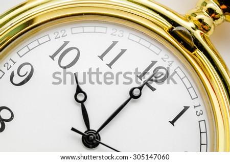 Close up gold pocket watch at ten oclock. - stock photo