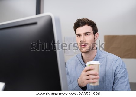 Close up Good Looking Office Man Holding a Cup of Coffee While Looking at his Computer Screen Seriously. - stock photo