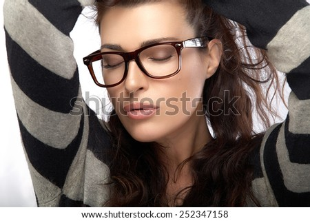 Close up gorgeous brunette fashion model girl with casual style clothing wearing trendy glasses, Holding her hair with closed eyes. Cool trendy eyewear portrait isolated on white background - stock photo