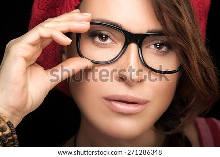 Close up Gorgeous Freckled Young Woman Holding her Eyeglasses While Looking at Camera. Cool Trendy Eye wear Portrait isolated on Black Background. - stock photo