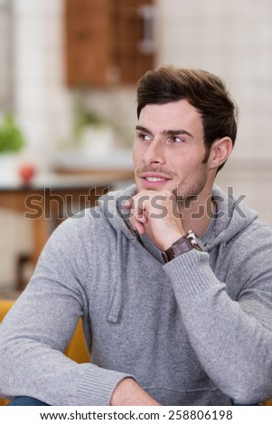 Close up Gorgeous Man in Gray Long Sleeve Tops Sitting on Couch with Hand on the Chin, Emphasizing Day Dreaming. - stock photo