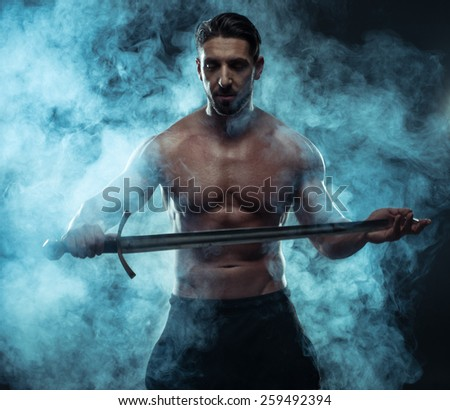Close up Gorgeous Shirtless Muscled Man Holding a Sword While Looking to the Left of the Frame on a Dark Blue Green Background. - stock photo