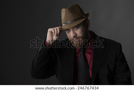 Close up Gorgeous Young Man in Business Suit Holding his Brown Hat While Looking at the Camera. Isolated on Gray Background - stock photo