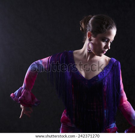 Close up Gorgeous Young Woman Posing in Elegant Red Violet Attire While Dancing Flamenco, Facing on Side. Captured in Studio on Abstract Gray Background. - stock photo