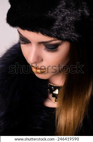 Close up Gorgeous Young Woman with Dark Eye Shadows and Gold Lips Make-up, Wearing Black Furry Winter Fashion - stock photo