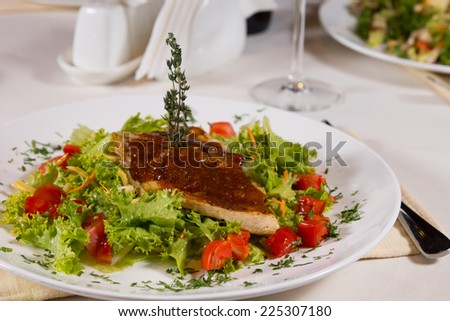 Close up Gourmet Appetizing Meaty Main Dish on Fresh Lettuce and Tomatoes. Served on the Table at the Restaurant. - stock photo