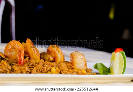 Close up Gourmet Appetizing Rice Dish with Prawns on the Top, Styled with Lemon on the Side. Prepared on White Rectangular Plate at the Restaurant. - stock photo