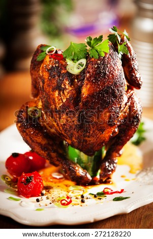 Close up Gourmet Appetizing Roast Whole Chicken on a White Plate with Herbs and Spices - stock photo