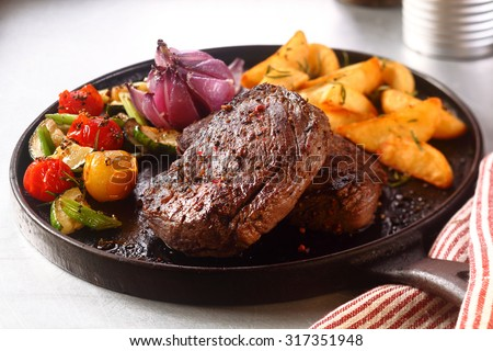 Close up Gourmet Appetizing Roasted Beef Steak with Potato Wedges and Other Vegetables on a Cast Iron Skillet. - stock photo