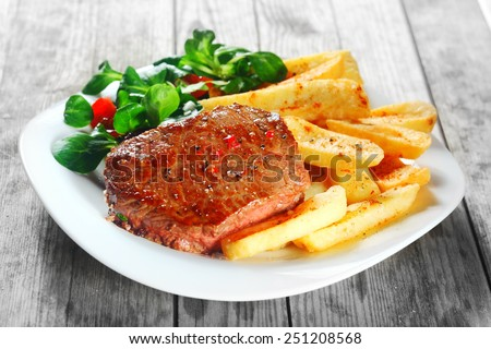 Close up Gourmet Flavored Grilled Meat with French Fries on White Plate, Placed on Wooden Table. - stock photo