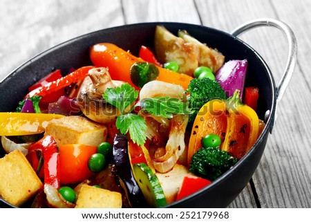 Close up Gourmet Healthy Main Dish on a Cooking Pan with Tofu, Broccoli, Mushrooms, Beans and Spices. Served on Wooden Table - stock photo