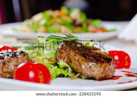 Close up Gourmet Main Course - Grilled Tender Juicy Meat with Veggies and Rosemary on White Plate. A Rich in Protein Recipe. - stock photo