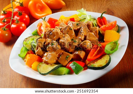 Close up Gourmet Saucy Cooked Meat or goulash with Fresh Veggies and Spices on a White Plate Served on Brown Wooden Table.