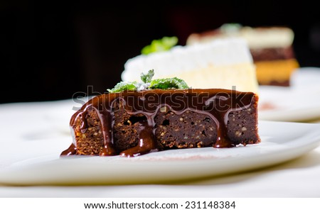 Close up Gourmet Sweet Chocolate Cake Slice with Chocolate Syrup on White Plate. Served on the Table. - stock photo