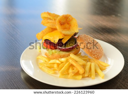 Close up Gourmet Tasty Burger Food with Cheese and Veggies Prepared on White Plate with Crispy Fried Fries, Served on Wooden Table. - stock photo