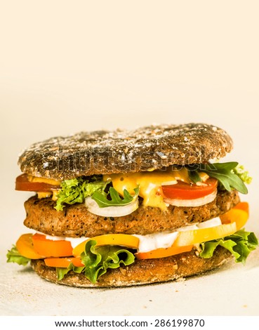 Close up Gourmet Tasty Hamburger with Fresh Veggies and Cheese on a Beige Background with Copy Space on the Top. - stock photo