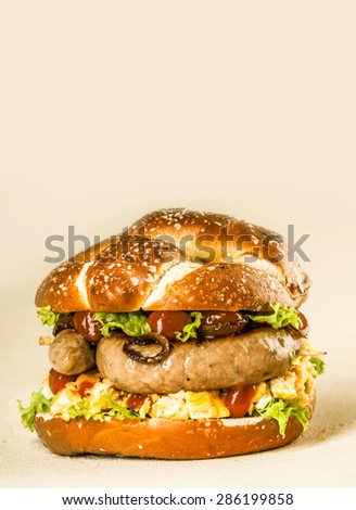 Close up Gourmet Tasty Sausage Burger with Fresh Veggies and Sauce on a Beige Background with Copy Space on the Top.