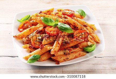 Close up Gourmet Tasty Spicy Italian Penne Pasta with Tomato and Herbs on a White Plate, Served on Top of a Wooden Table. - stock photo