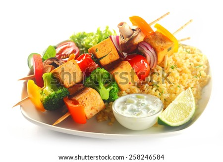 Close up Gourmet Tofu Kebabs on Flavored Yellow Rice with Mustard Sauce and Lemon on White Plate. Isolated on White. - stock photo