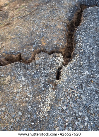 Close up gravel on the dirt road, which cracks due to water erosion and land subsidence. - stock photo