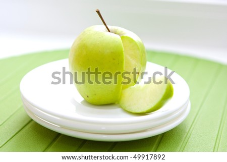 close up green apple and a slice on the white plates - stock photo