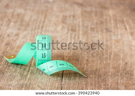 Close up green measuring tape on wooden table background