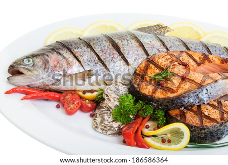Close up Grilled trout and salmon steaks with vegetables and oysters - stock photo