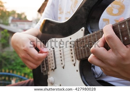 Close up guitarist plays at sunset time with outdoor background. - stock photo